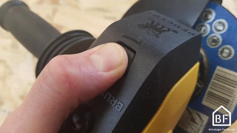 bouton de blocage de l'arbre moteur d'une meuleuse