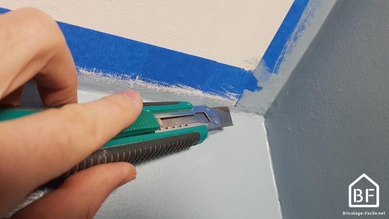 découpe de la peinture sur le scotch de peintre